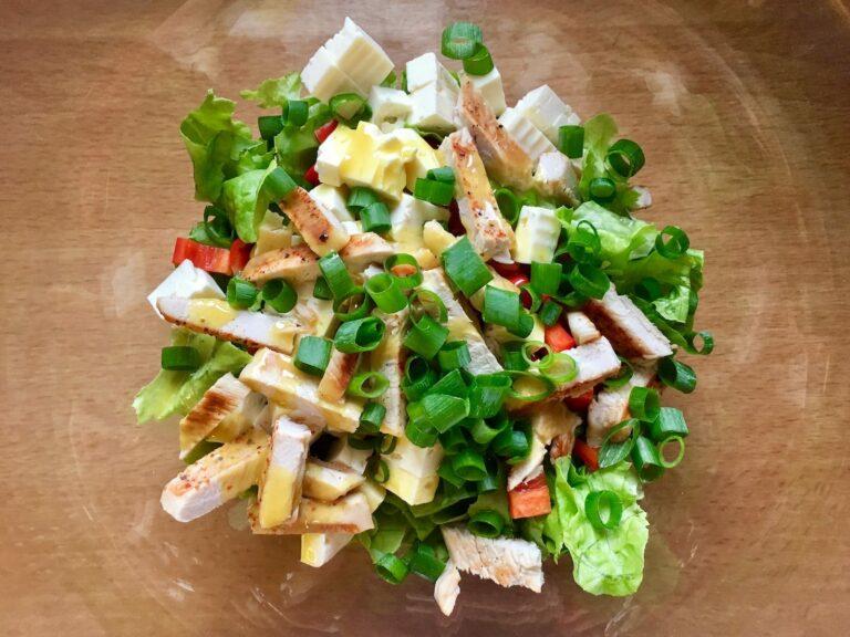 Salat mit gegrillten Putenbrust Streifen anrichten