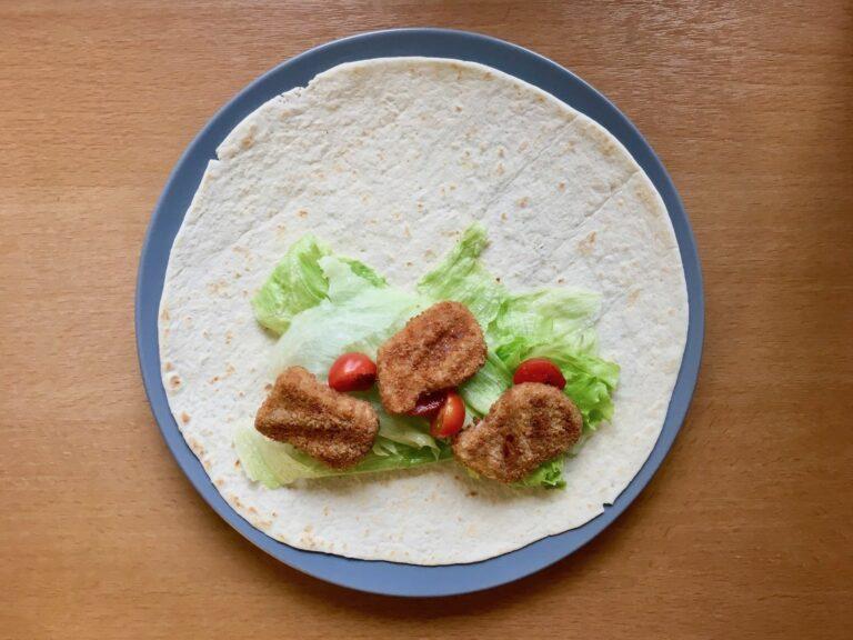 Tortilla mit Salat Tomaten und Chicken Nuggets belegen